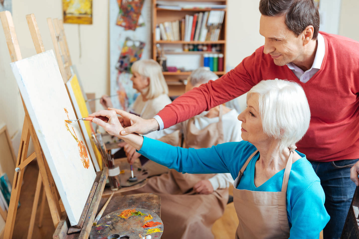 artist helping elderly woman in painting retreat