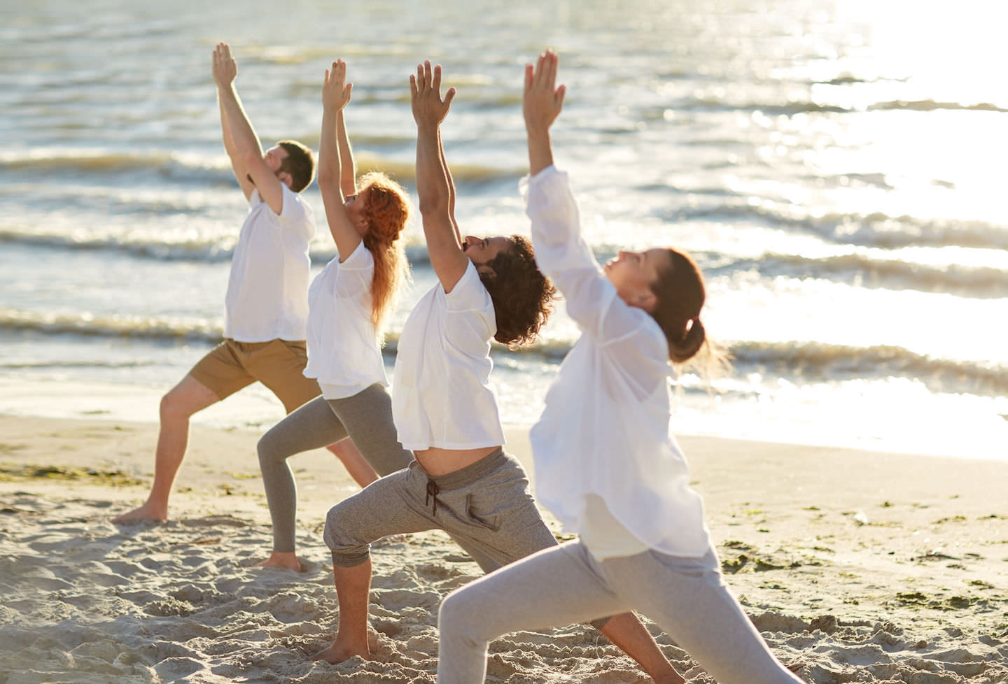 group of people making yoga exercises on beach retreat